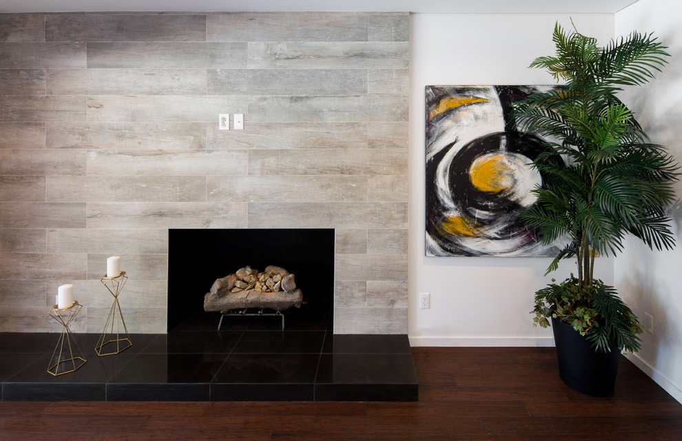 Example of a large trendy open concept dark wood floor and brown floor family room design in Los Angeles with white walls, a standard fireplace, a tile fireplace and no tv