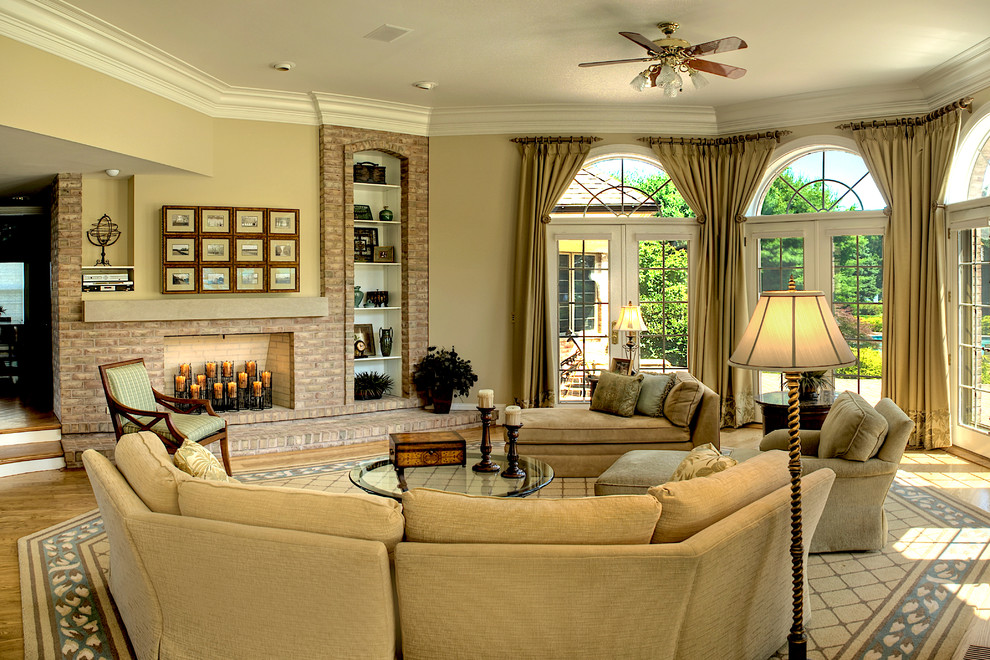 Large elegant open concept medium tone wood floor and beige floor family room photo in DC Metro with beige walls, a standard fireplace and a brick fireplace