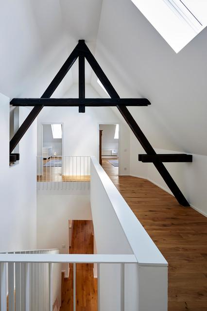 Großer Moderner Flur mit weißer Wandfarbe, braunem Holzboden und braunem Boden in Köln