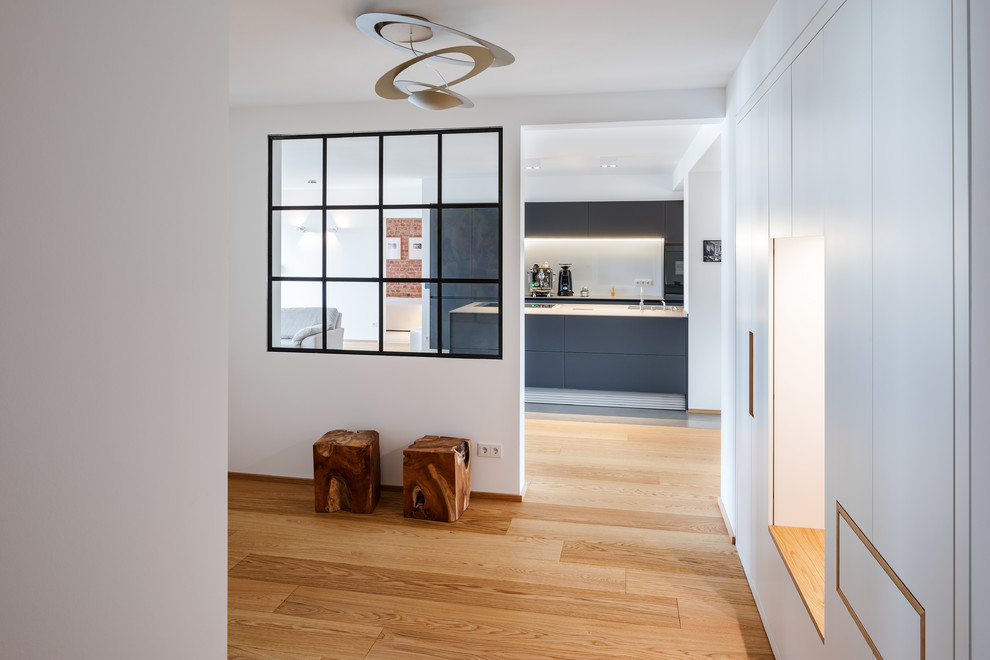 Inspiration for a large industrial medium tone wood floor and brown floor hallway remodel in Essen with white walls