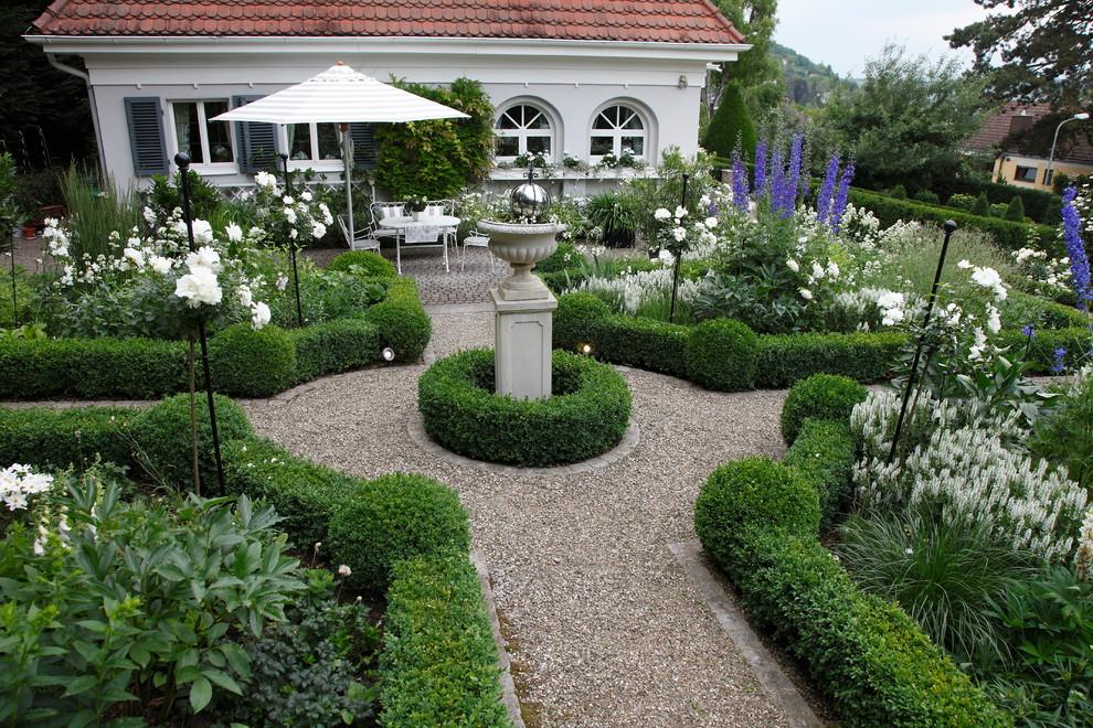 Foto di un grande giardino formale classico esposto in pieno sole dietro casa con un ingresso o sentiero e ghiaia