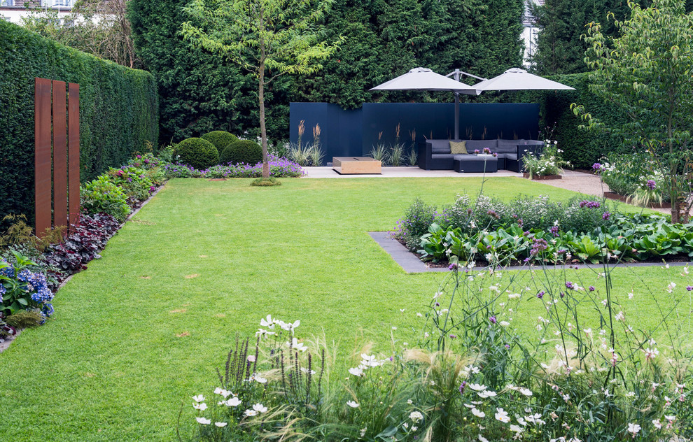 Inspiration for a large contemporary partial sun backyard concrete paver landscaping in Dusseldorf for summer.