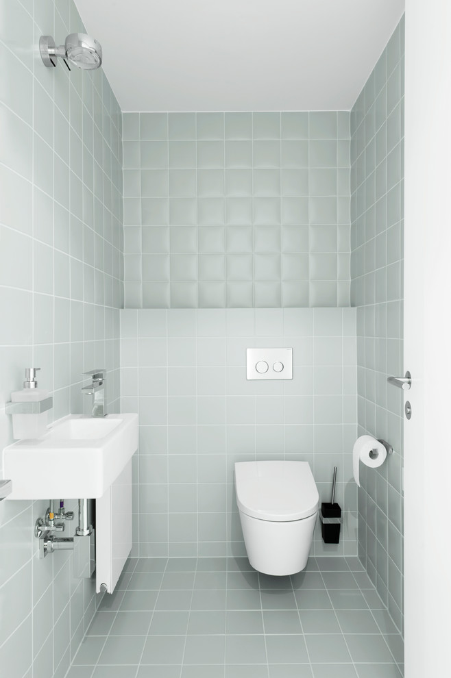 Inspiration for a small modern ceramic tile and gray tile ceramic tile and gray floor powder room remodel in Other with a wall-mount toilet, a wall-mount sink and gray walls