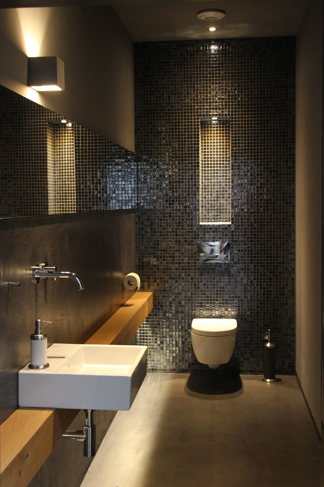 Powder room - small modern black tile and mosaic tile concrete floor and gray floor powder room idea in Cologne with a two-piece toilet, black walls, a wall-mount sink, wood countertops and brown countertops