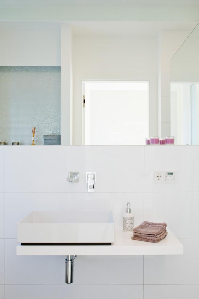 Imagen de aseo actual, de tamaño medio, con baldosas y/o azulejos blancos, paredes blancas, lavabo sobreencimera y baldosas y/o azulejos de cerámica