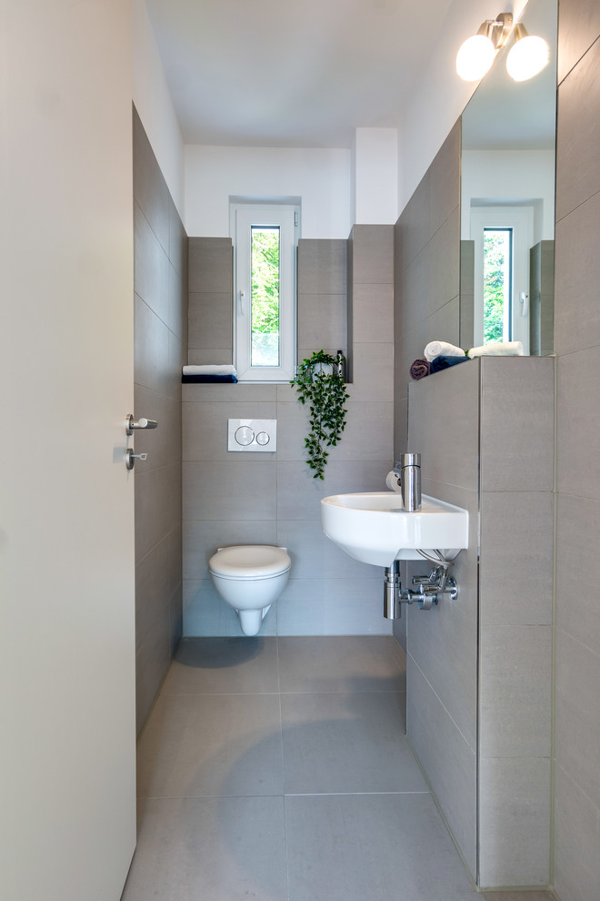 Example of a small danish beige tile and cement tile cement tile floor and beige floor powder room design in Hamburg with a wall-mount toilet, white walls and a wall-mount sink