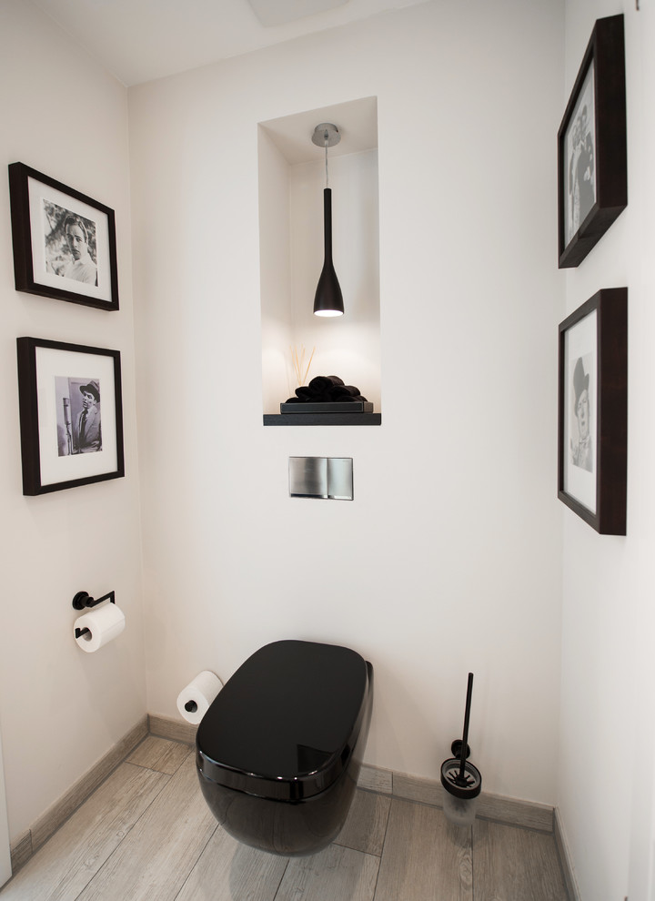 Powder room - small contemporary medium tone wood floor powder room idea in Dortmund with a wall-mount toilet and white walls