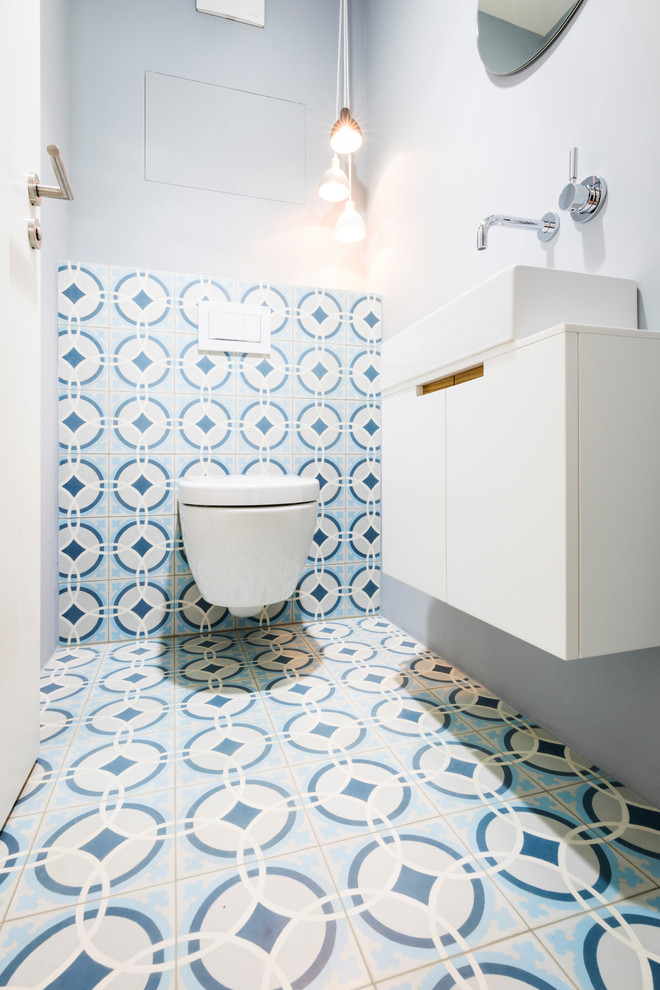 Example of a small trendy blue tile, white tile and cement tile cement tile floor and multicolored floor powder room design in Munich with flat-panel cabinets, white cabinets, a two-piece toilet, gray walls and a vessel sink