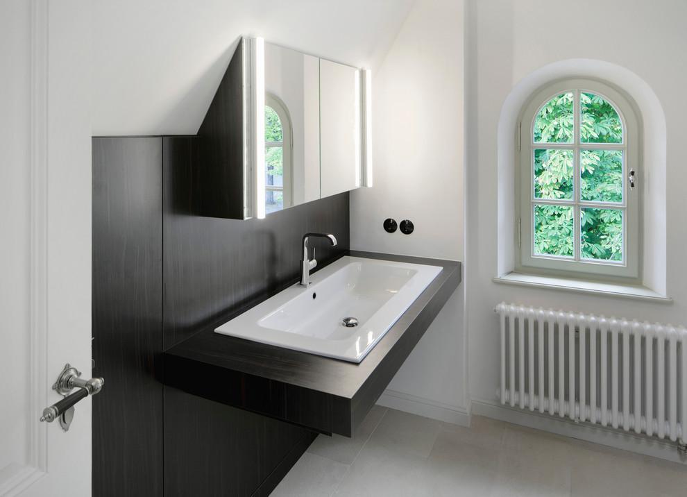 Foto de aseo clásico con puertas de armario de madera en tonos medios, lavabo encastrado, encimera de madera y encimeras negras