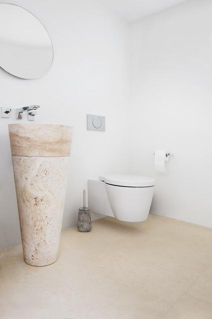 Aménagement d'un petit WC et toilettes moderne avec un WC suspendu, un mur blanc, un sol en calcaire et un lavabo de ferme.