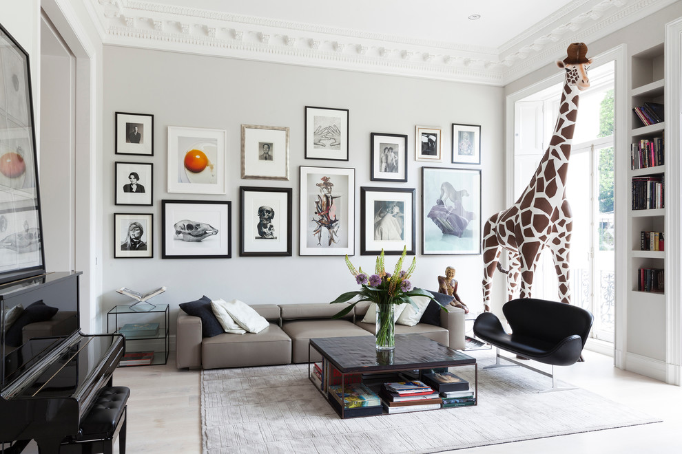 Example of an eclectic enclosed light wood floor family room design in London with a music area and gray walls