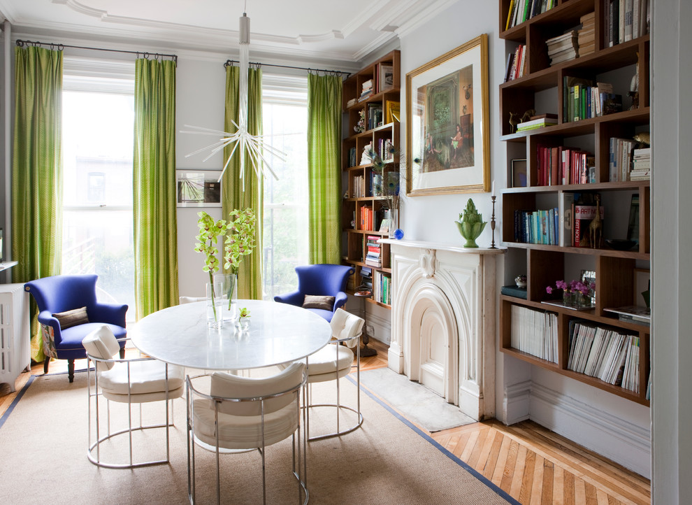 Inspiration for a contemporary enclosed light wood floor family room library remodel in London with white walls, a standard fireplace and no tv