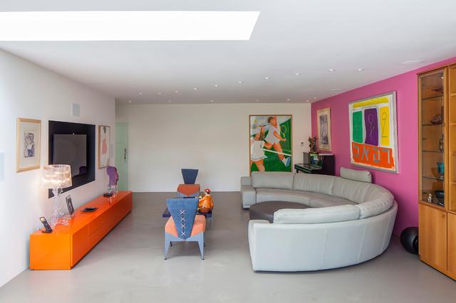 Modelo de sala de estar cerrada, contemporánea, grande, sin chimenea, con suelo de cemento, televisor colgado en la pared y paredes multicolor