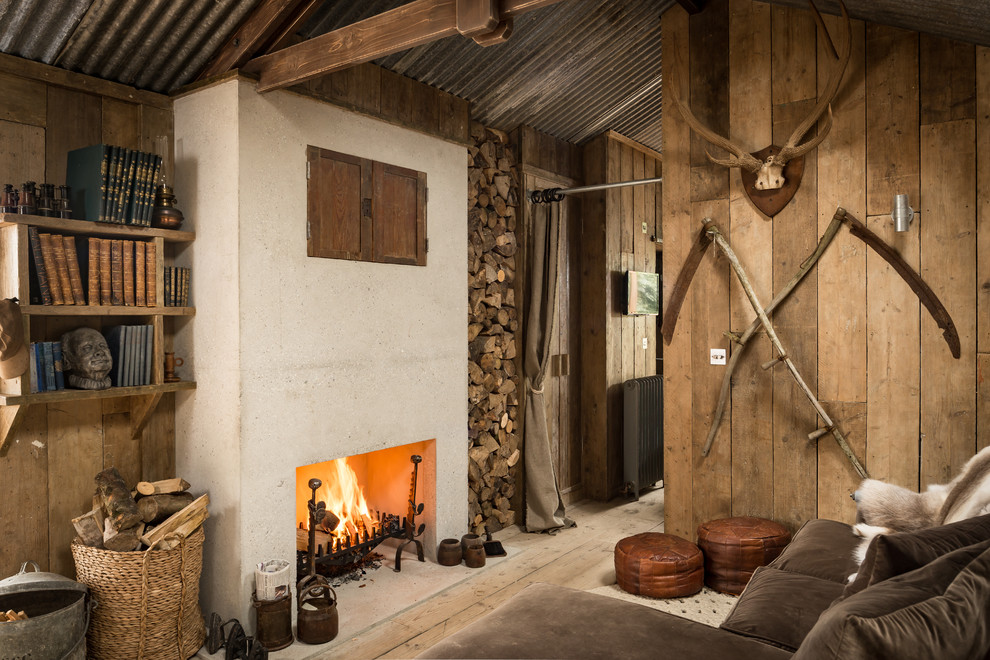 Photo of a rustic family and games room in Cornwall with a reading nook, light hardwood flooring, a standard fireplace, a concealed tv and a concrete fireplace surround.