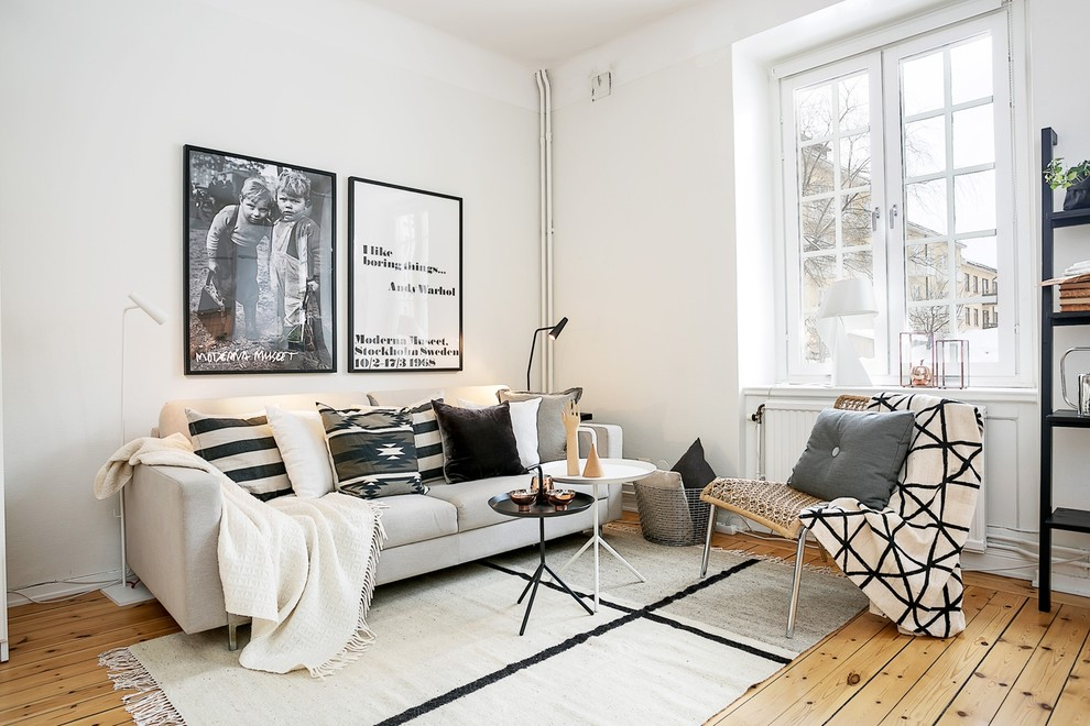 Inspiration for a mid-sized scandinavian open concept medium tone wood floor family room remodel in Stockholm with white walls, no fireplace and no tv