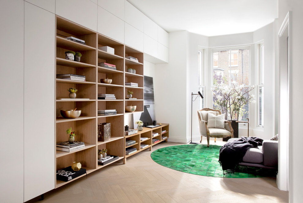 Family room library - mid-sized contemporary open concept light wood floor family room library idea in London with white walls and no tv
