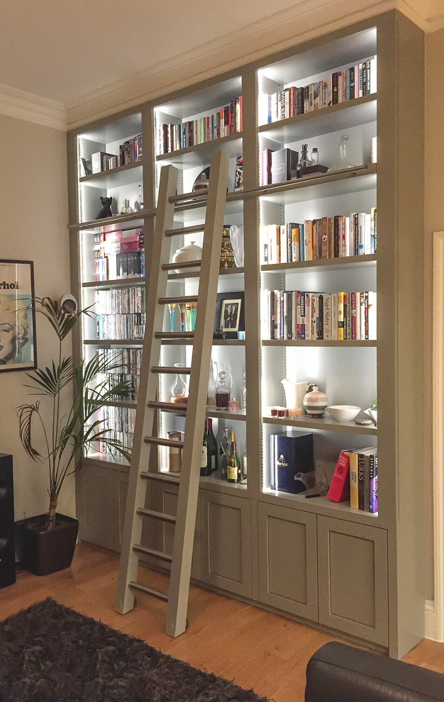 Example of a transitional light wood floor family room library design in London