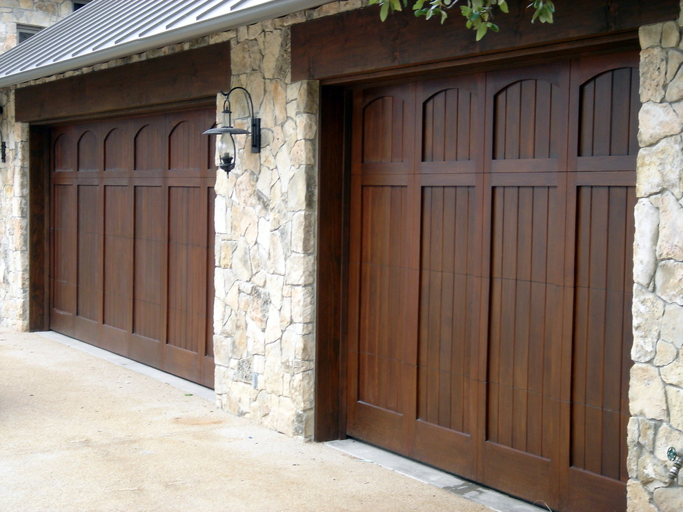 Example of a large tuscan attached two-car garage design in Austin