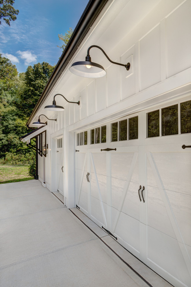 Example of a farmhouse attached three-car garage design in Charlotte