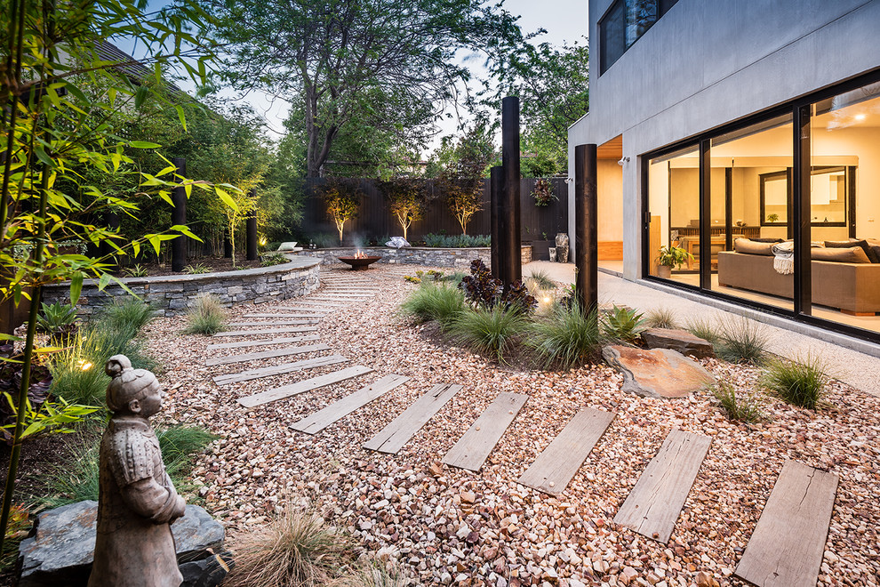 Inspiration for a large asian partial sun backyard gravel landscaping in Melbourne with a fire pit.