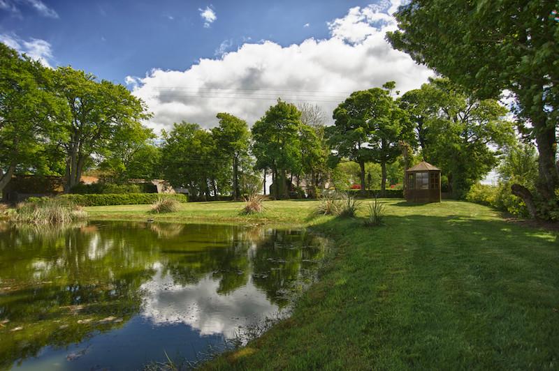 Foto de jardín tradicional, grande, en verano, en patio delantero, con jardín francés y exposición parcial al sol