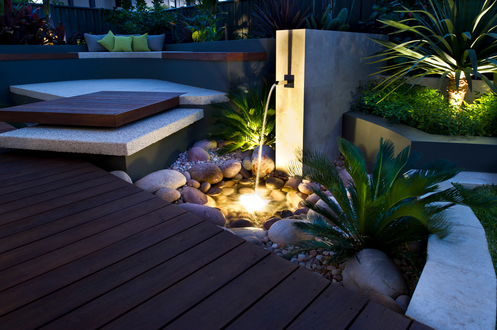 This is an example of a small contemporary full sun backyard water fountain landscape in Perth with decking.