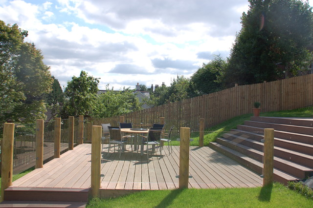Beautiful hardwood deck surrounded by round timber posts for Garden decking glass panels