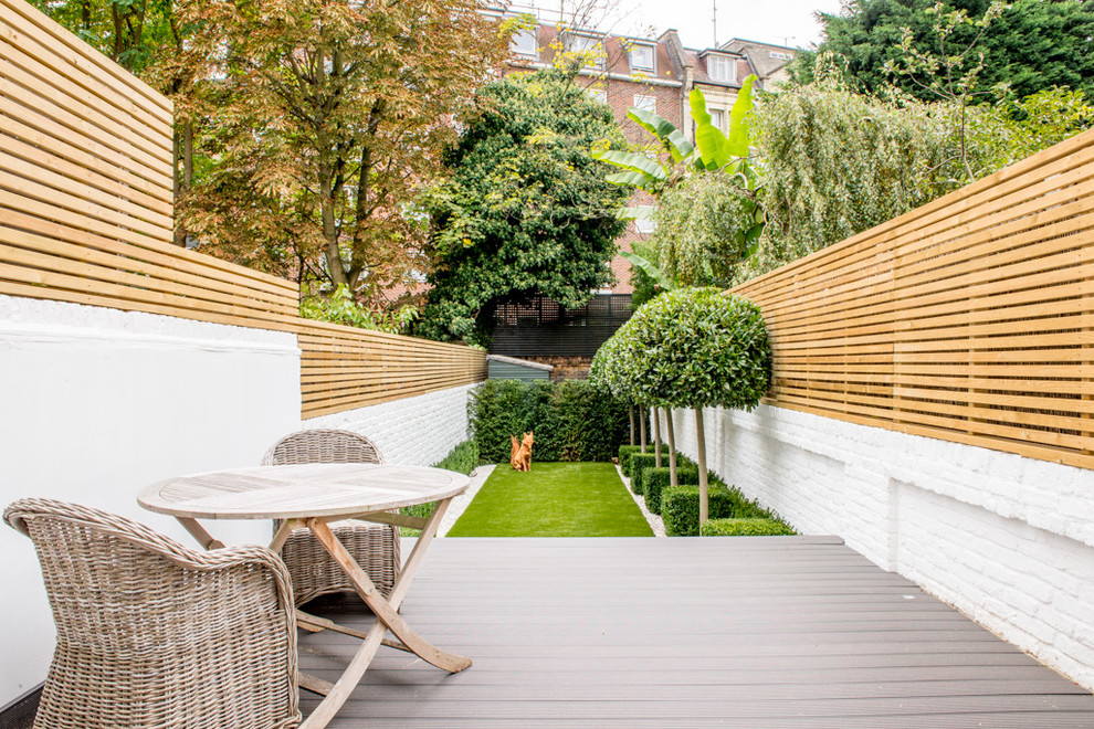 Photo of a small transitional full sun backyard formal garden in London with decking.