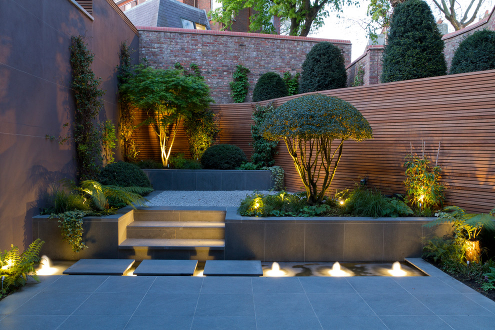 Photo of an asian side yard stone landscaping in London.