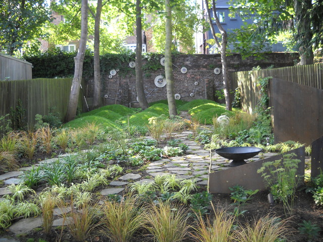 Inspiration for an eclectic backyard landscaping in London with a fire pit.
