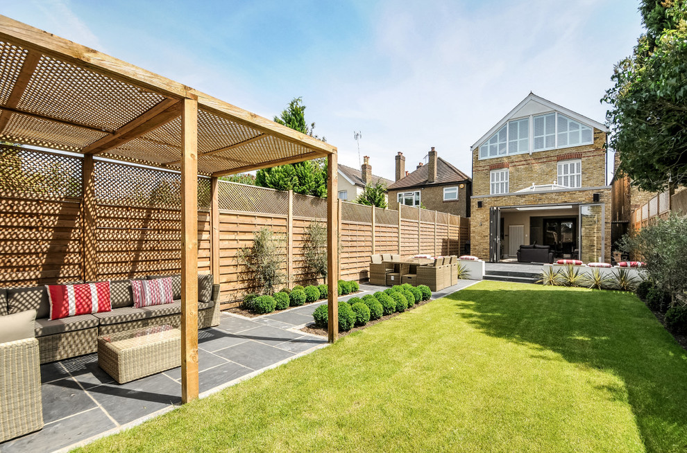 Photo of a transitional partial sun backyard landscaping in London.