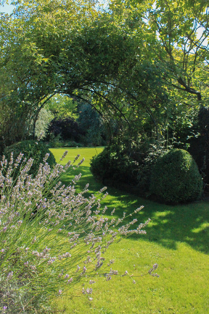 Inspiration for a traditional formal partial sun garden for spring in Sussex with a garden path.