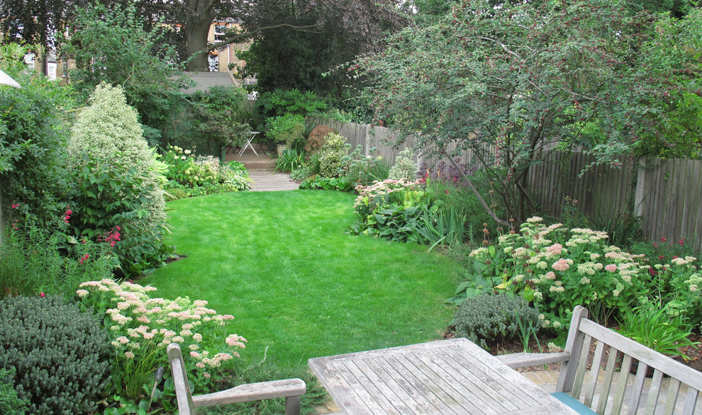 This is an example of a large traditional back full sun garden for summer in London with decking.