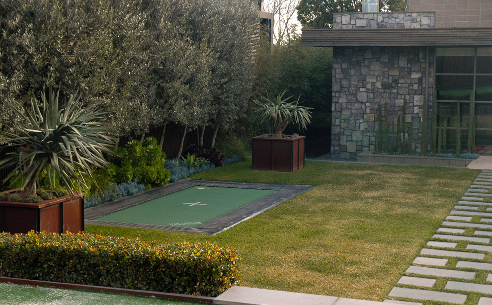 Photo of a large contemporary backyard partial sun garden in Melbourne with natural stone pavers.