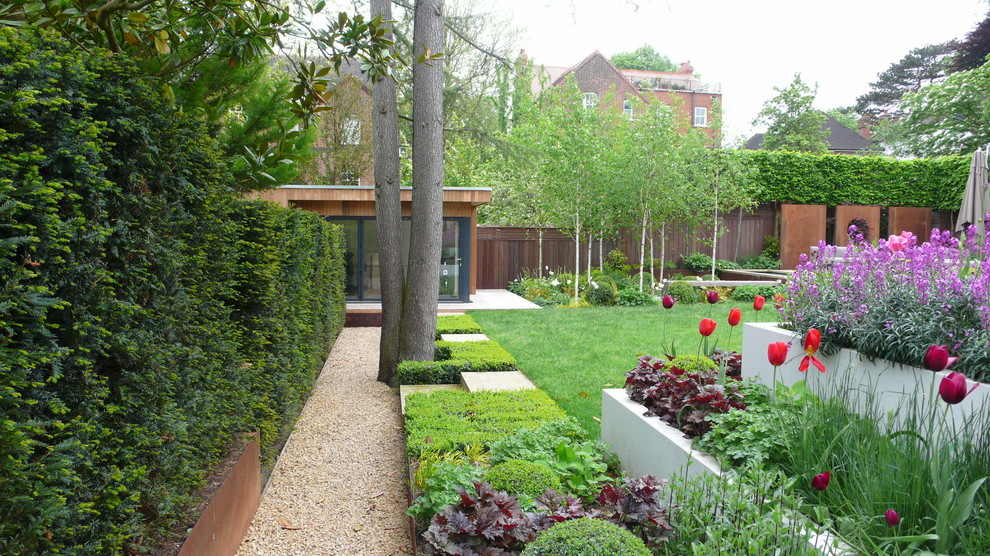 Inspiration for a large contemporary partial sun backyard gravel landscaping in London.