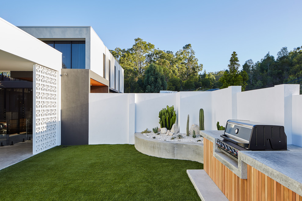 Design ideas for a modern backyard garden in Gold Coast - Tweed with concrete pavers.