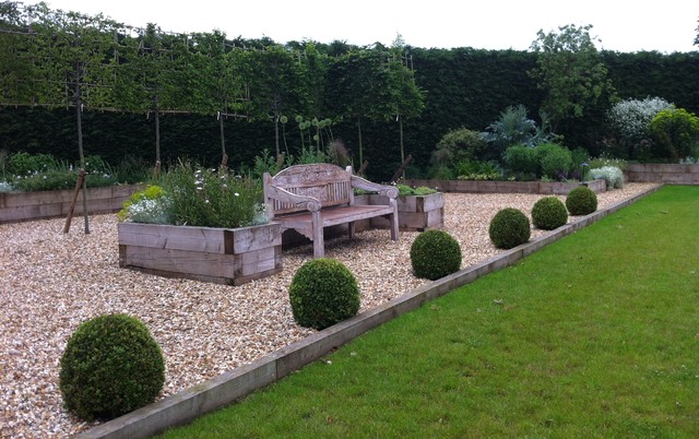 Hornbeam High panel hedging behind an oversized antique bench and