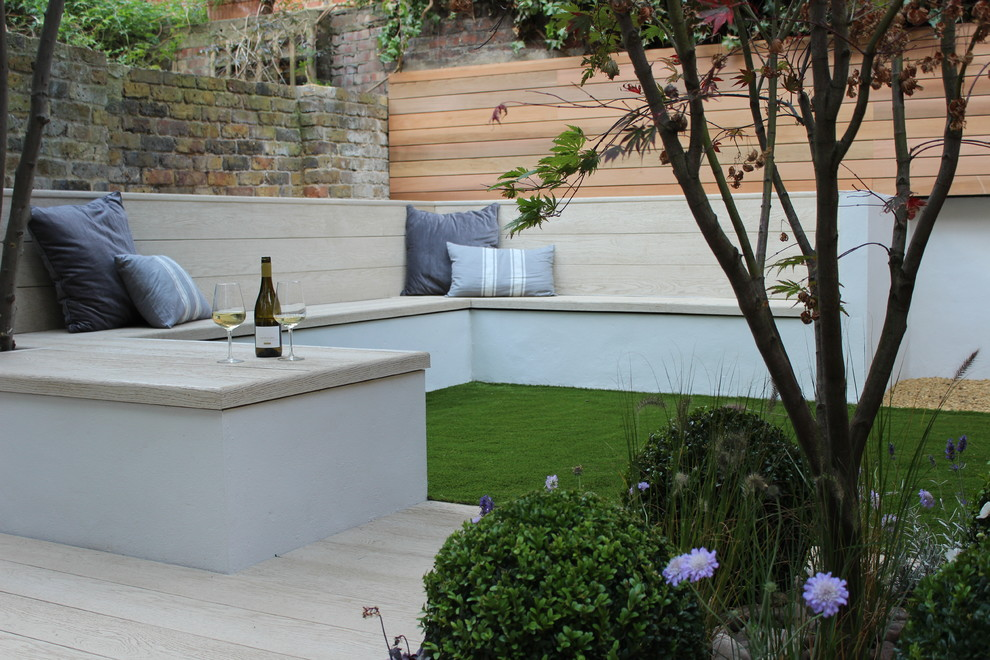 Design ideas for a small contemporary partial sun backyard landscaping in London with decking.