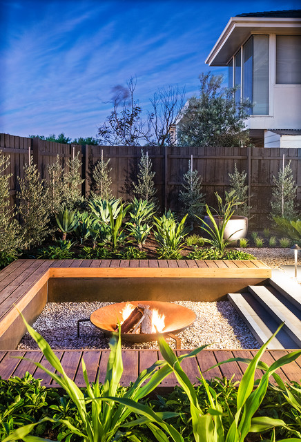 Photo of a mid-sized contemporary backyard full sun garden in Melbourne with a fire feature and gravel.