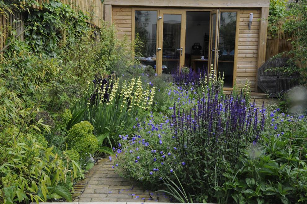 Photo of a small contemporary partial sun backyard brick landscaping in London.