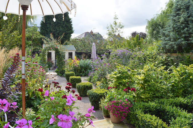 This is an example of a medium sized traditional full sun garden in Other with gravel.