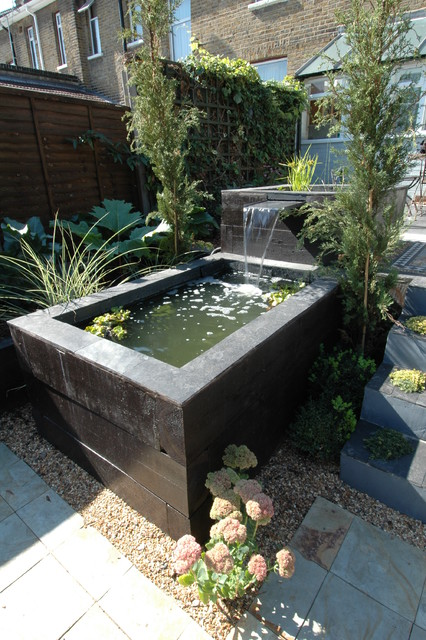 Raised railway sleeper pool and slate water feature for Raised garden pond ideas uk