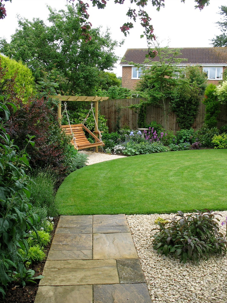 Design ideas for a mid-sized traditional full sun backyard gravel landscaping in Other for summer.