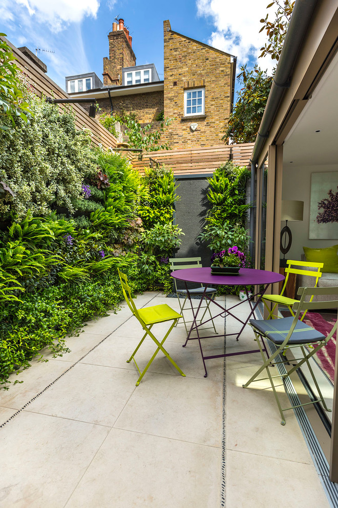 Design ideas for a small contemporary partial sun backyard stone landscaping in London for summer.