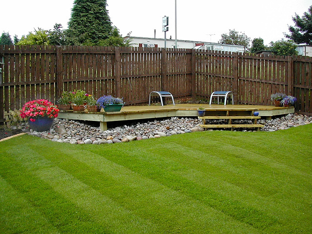 Small raised corner deck with a beach pebble border for Garden decking near me