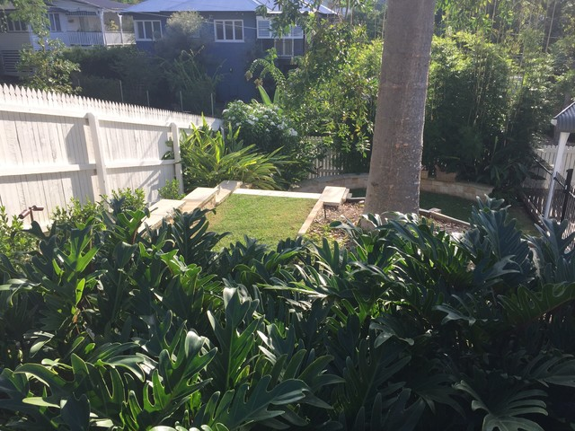 Design ideas for a mid-sized tropical side yard partial sun formal garden in Brisbane with natural stone pavers.