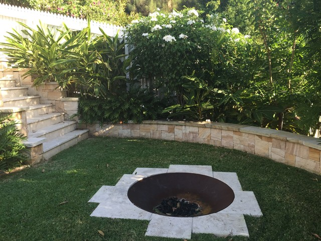 Inspiration for a mid-sized tropical backyard partial sun formal garden in Brisbane with natural stone pavers and a fire feature.