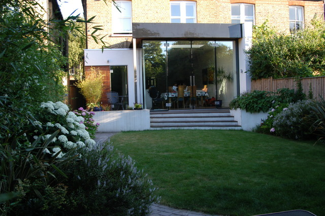 This is an example of a medium sized contemporary back garden in London with decking.