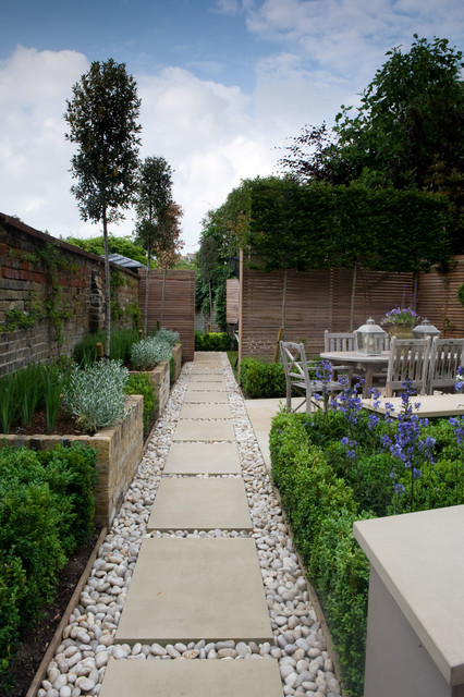 Design ideas for a small traditional shade backyard stone landscaping in London.