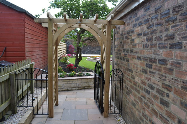 Wooden Arch With Wrought Iron Gate And Panels Creates A